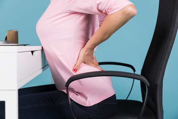 Mujer que sufre de dolor de espalda mientras está sentado en una silla