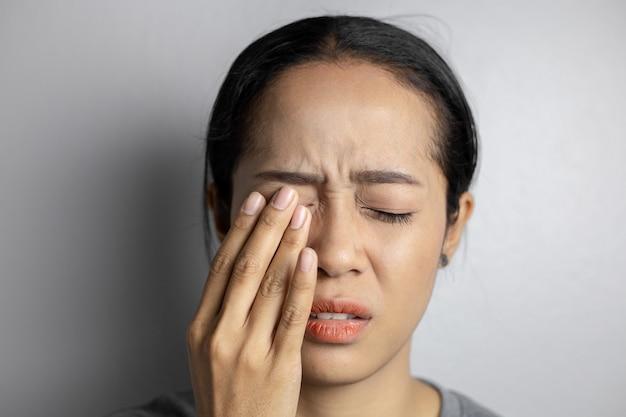 Mujer que sufre de dolor intenso en los ojos.