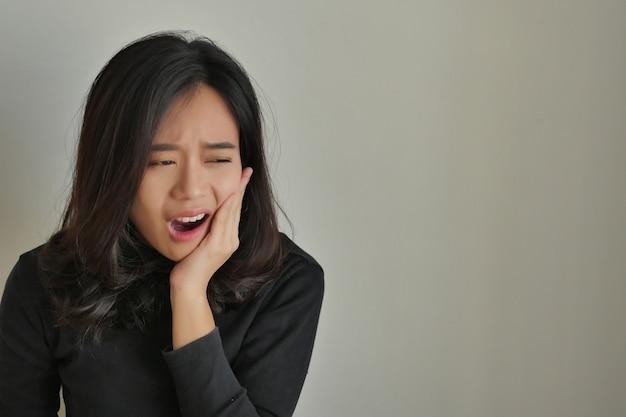Mujer que sufre dolor de muelas, niña con caries, sensibilidad, concepto de tratamiento de cuidado dental