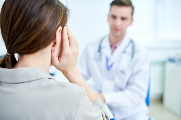 Mujer que sufre de dolor de oído