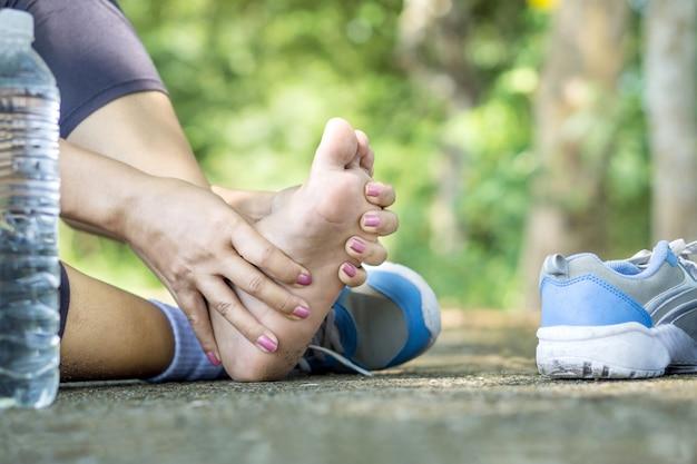 Mujer que sufre de dolor en el pie durante el deporte.