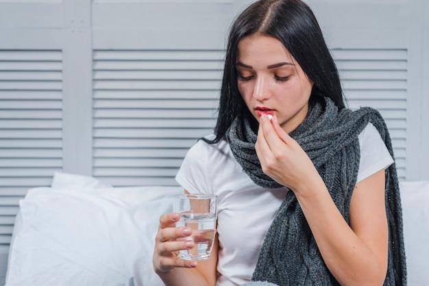 Mujer que sufre de frío sosteniendo vaso de agua tomando medicina
