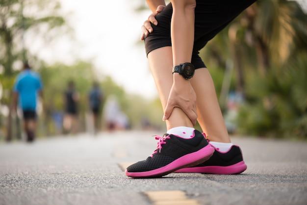 Mujer que sufre de una lesión en el tobillo mientras hace ejercicio. concepto de lesión en el funcionamiento.