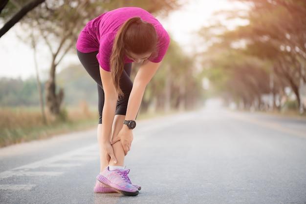Mujer que sufre de una lesión en el tobillo mientras hace ejercicio.