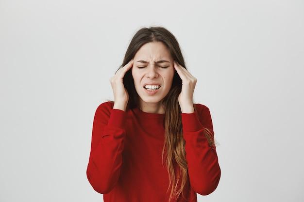 Mujer que sufre migraña, frota las sienes y hace muecas con los ojos cerrados, siente dolor de cabeza