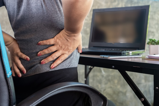 Mujer que sufre de síndrome de oficina con dolor lumbar