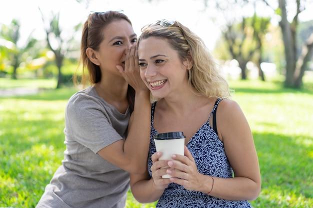Mujer que susurra secreto a la novia sonriente en el parque