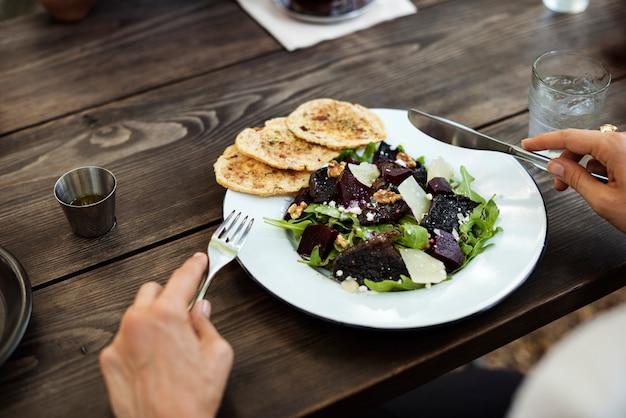 Mujer que tiene comida de ensalada en el restaurante
