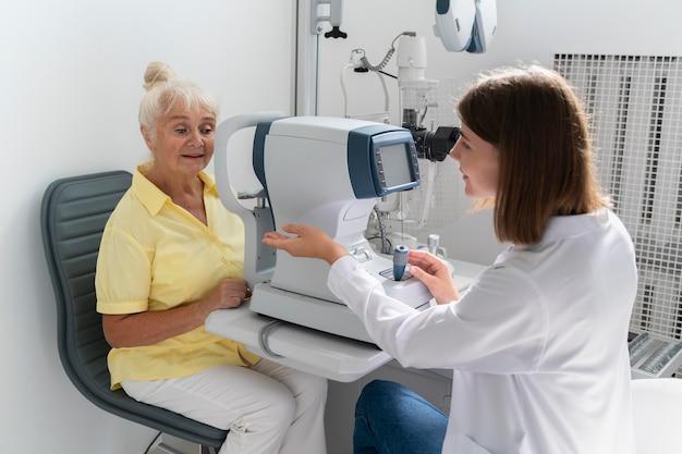 Mujer que tiene un control de la vista en una clínica de oftalmología