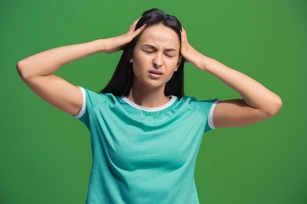 Mujer que tiene dolor de cabeza. aislado sobre verde.