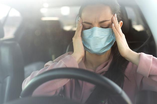 Mujer que tiene un dolor de cabeza en el auto