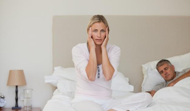Mujer que tiene un dolor de cabeza mientras su marido está durmiendo