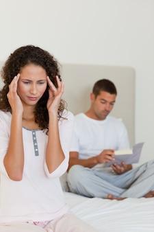 Mujer que tiene un dolor de cabeza mientras su marido está leyendo