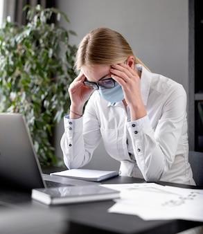 Mujer que tiene dolor de cabeza mientras usa una mascarilla