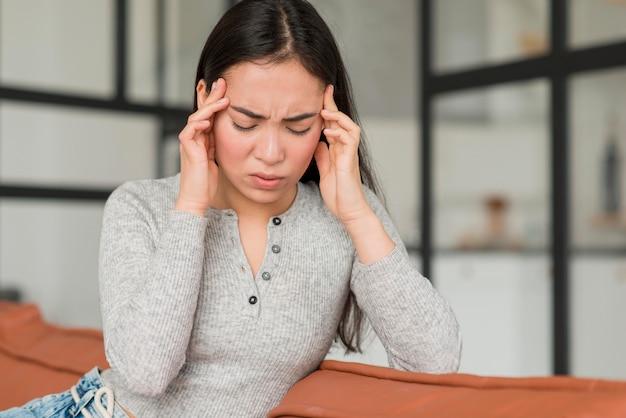 Mujer que tiene dolor de cabeza