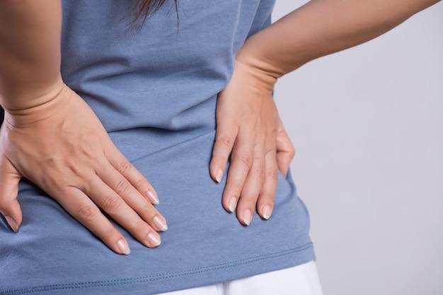 Mujer que tiene dolor en la espalda lesionada. asistencia sanitaria y dolor de espalda.