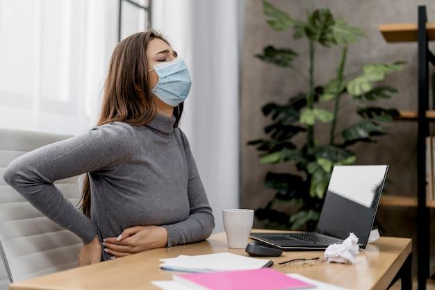 Mujer que tiene dolor de espalda mientras trabaja en casa