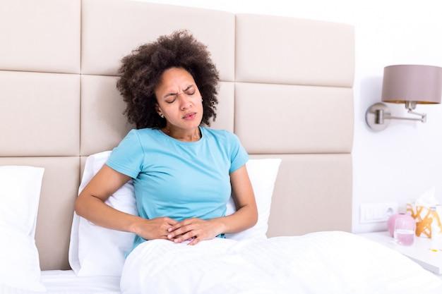 Mujer que tiene dolor de estómago doloroso en la cama, período menstrual