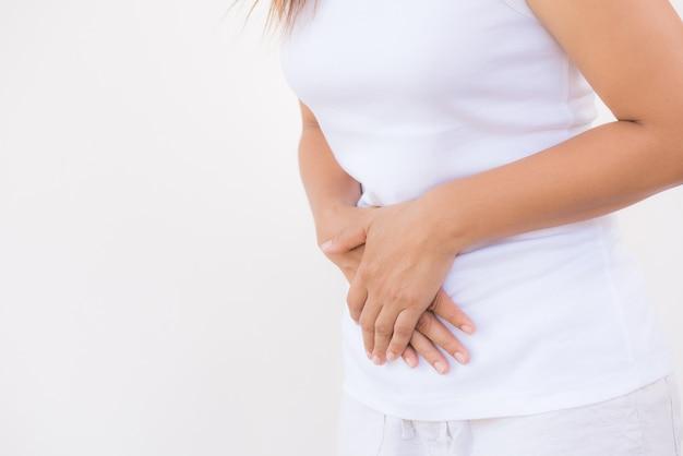 Mujer que tiene dolor de estómago doloroso en el fondo blanco. concepto de hinchazón del abdomen.