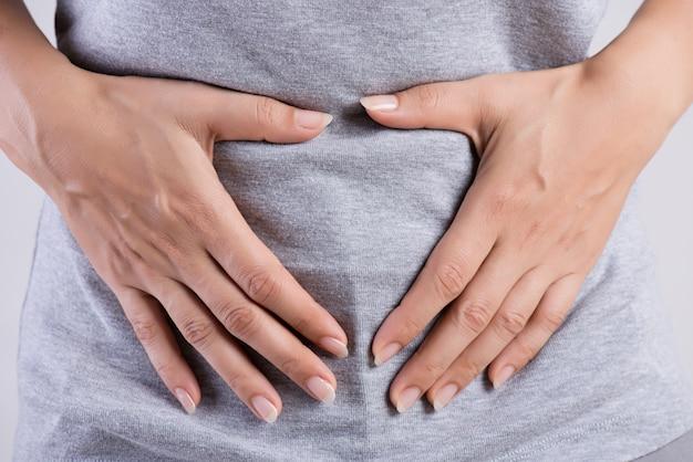 Mujer que tiene dolor de estómago doloroso. gastritis crónica. concepto de hinchazón del abdomen.