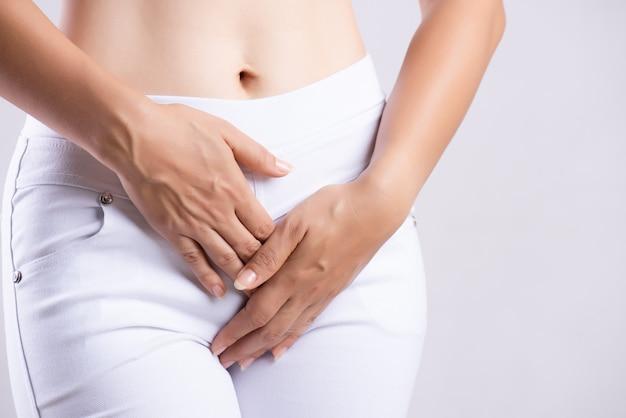 Mujer que tiene dolor de estómago doloroso, manos que sostienen presionando su entrepierna parte inferior del abdomen