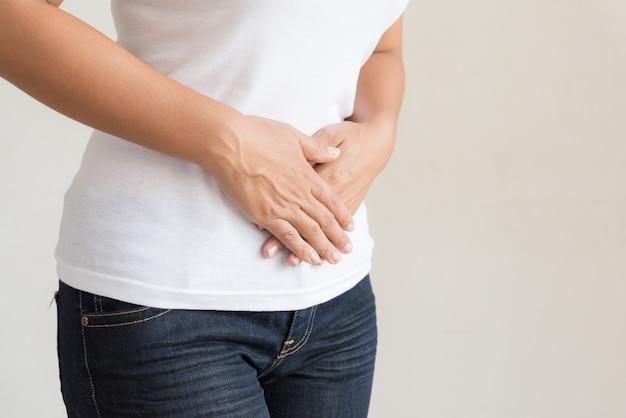 Mujer que tiene dolor de estómago doloroso