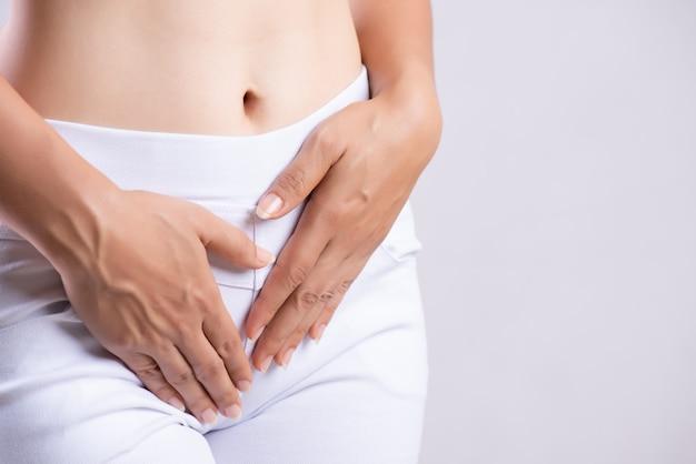 Mujer que tiene dolor de estómago, manos presionando su entrepierna parte inferior del abdomen