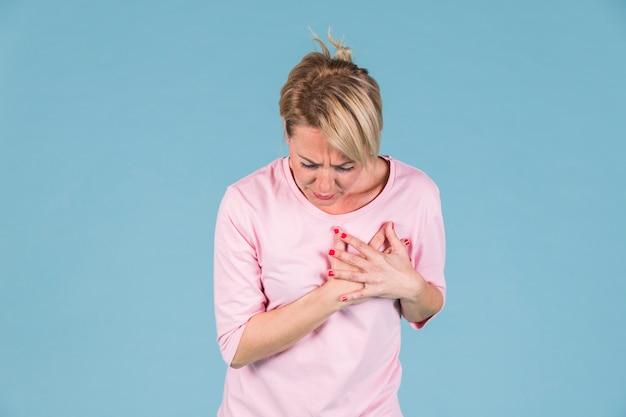 Mujer que tiene dolor en el pecho de pie contra el fondo azul