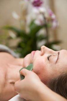 Mujer que tiene un masaje facial gua sha con masajeador de piedra de jade natural