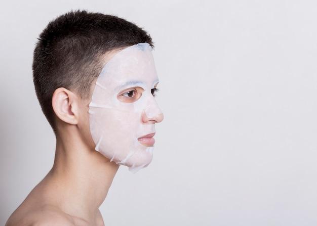 Mujer que tiene una máscara blanca en la cara