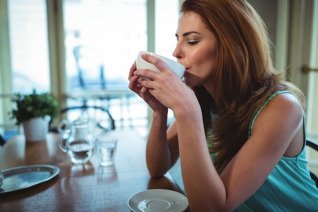 Mujer que tiene una taza de café en la cafetería ©