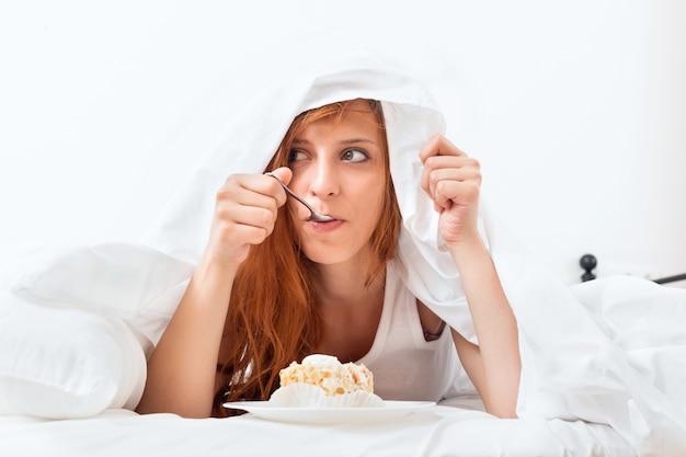 Mujer que tiene torta dulce en la cama
