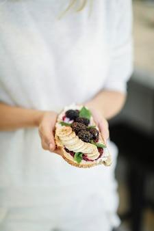 Mujer que tiene una tostada con mermelada de moras y queso crema vegano