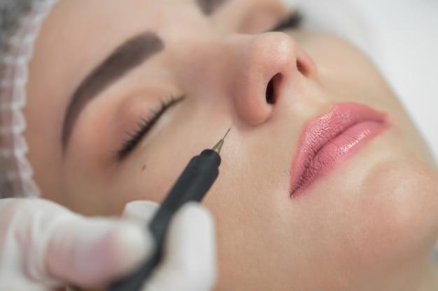 Mujer que tiene tratamiento cosmético de belleza galvánica