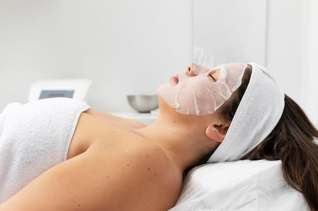 Mujer que tiene un tratamiento de cuidado de la piel facial