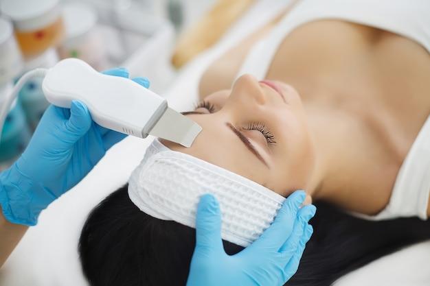 Mujer que tiene tratamiento facial en salón de belleza