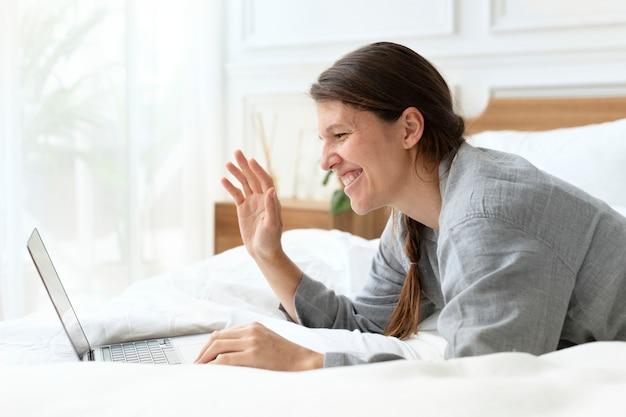 Mujer que tiene una videollamada en la cama