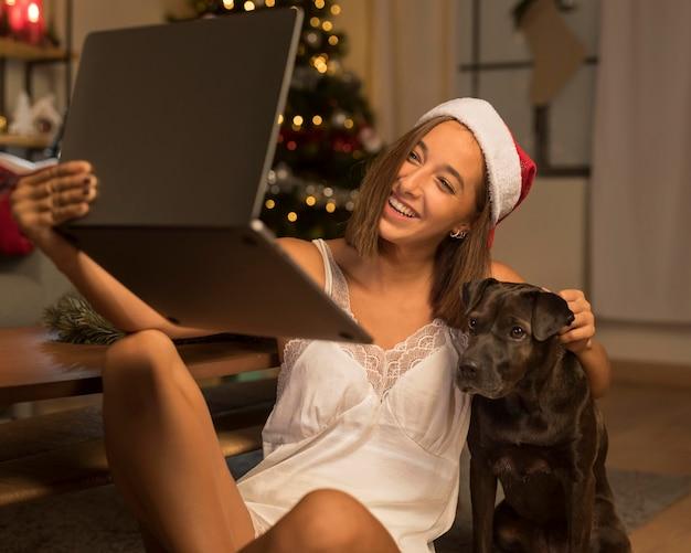 Mujer que tiene una videollamada en navidad con su perro y gorro de papá noel