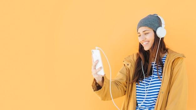 Mujer que tiene videollamada en el teléfono celular con auriculares contra la superficie amarilla