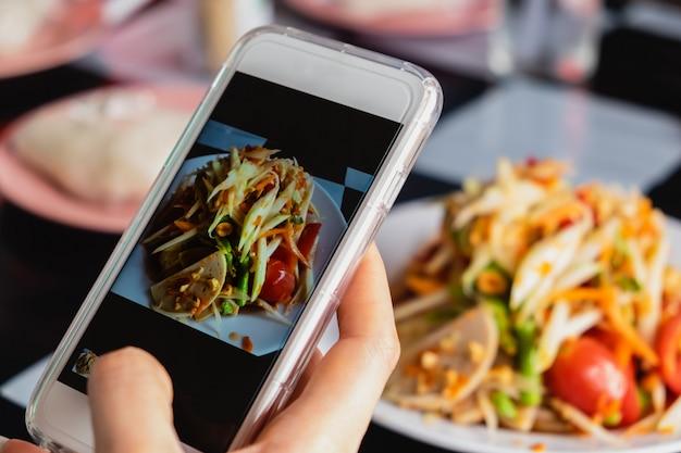 Mujer que toma una foto de ensalada de papaya verde tailandesa con teléfono inteligente