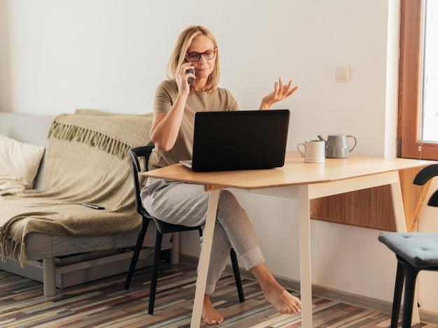 Mujer que trabaja en casa durante la cuarentena con computadora portátil y teléfono inteligente