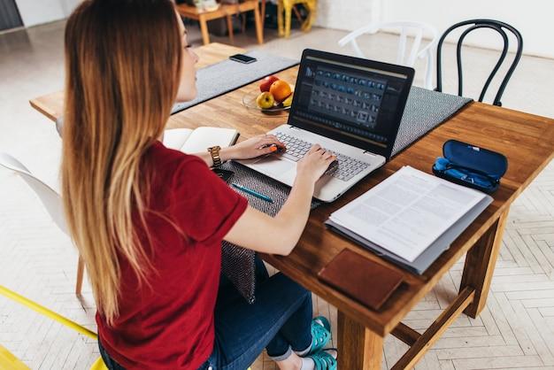 Mujer que trabaja en casa usando la computadora portátil sentada a la mesa en la cocina, autónomo que trabaja en el cuaderno.
