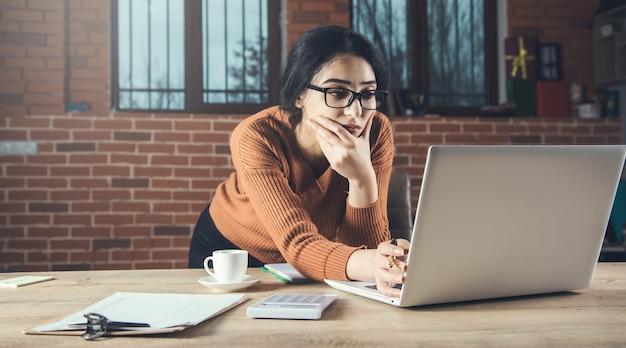 Mujer que trabaja en la computadora en el escritorio de oficina