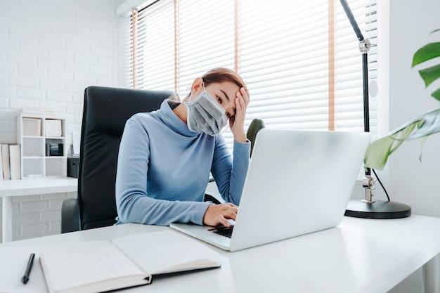 Mujer que trabaja con la computadora con máscara protectora