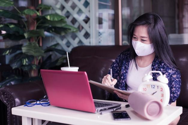 Mujer que trabaja en la computadora portátil en casa con una mascarilla médica para proteger para proteger 2019: ncov, covid 19 o corona virus.
