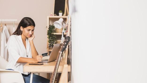Mujer que trabaja en la computadora portátil en casa