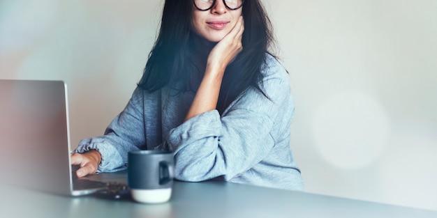 Mujer que trabaja en una computadora portátil en casa
