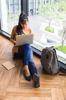 Mujer que trabaja en la computadora portátil cerca de la ventana