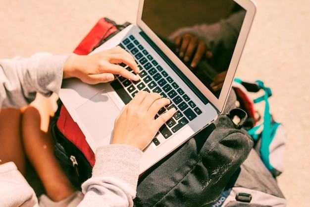 Mujer que trabaja en la computadora portátil colocada en las mochilas
