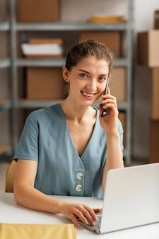 Mujer que trabaja en la computadora portátil y hablando por teléfono